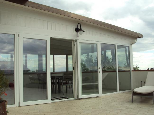 Particolare della porta finestra in PVC bianco con apertura scorrevole per la veranda in terrazzo