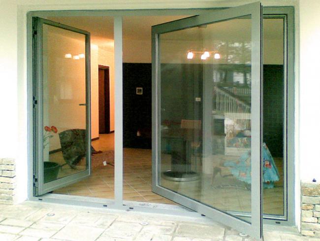 Installazione di grandi serramenti in alluminio con chiusura a battente, profilo rompitratta ed apertura a bilico