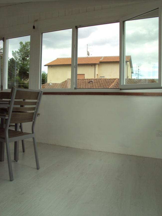 Pavimento in parquet laminato grigio e infissi in PVC bianco per la copertura a veranda del terrazzo.
