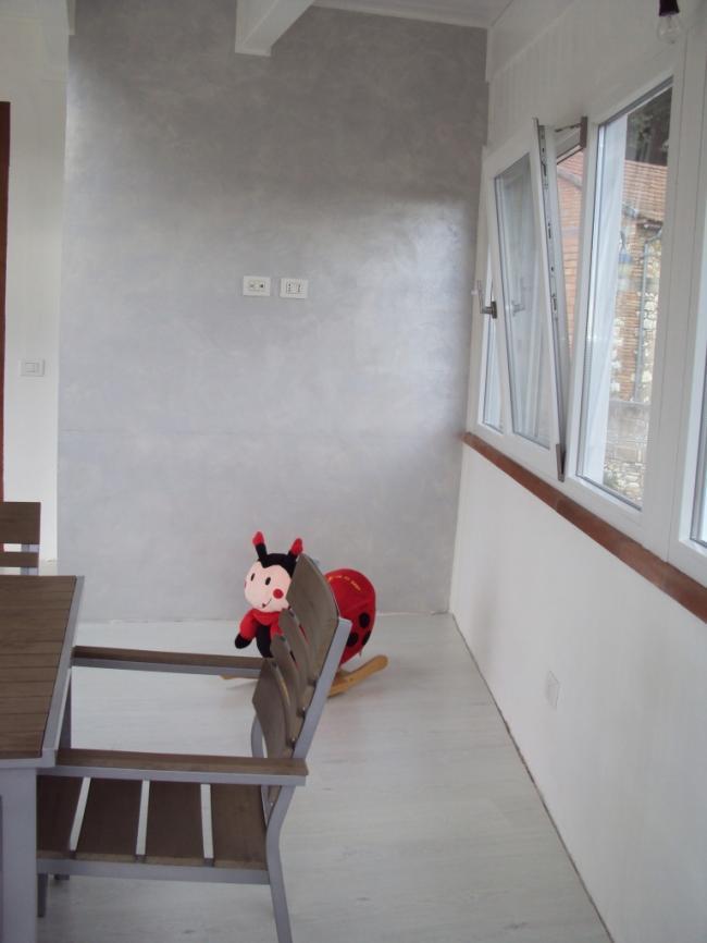 Interno di una veranda in terrazzo - Chiusura con infissi in PVC ad apertura Wasistas